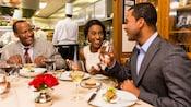 3personas comiendo y bebiendo en una mesa cerca de una cocina con 4chefs