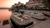 Two Sun Tracker® pontoon boats docked alongside Disney's Grand Floridian Resort & Spa