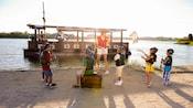 Una miembro del elenco y 7 niños, todos disfrazados de bucaneros, esperan a que su barco pirata llegue a la orilla
