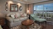 Uma área de estar mobiliada com um sofá, mesa de café, poltrona e pufe combinando, com um pátio com vista para o lago