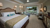 Uma cama queen-size ao lado de uma mesa de cabeceira e um sofá-cama tamanho queen em um quarto com portas para a área e vista para o jardim