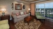 Uma área de estar mobiliada com um sofá, mesa de café, poltrona e 3pufes, com uma vista da varanda