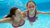 A mother swims underwater with her daughter who's wearing goggles
