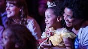 A smiling young girl wears a Disney Princess costume and sits on her mother's lap