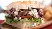 A sandwich stuffed with caramelized onions, roast beef, blue cheese, tomato slices and lettuce