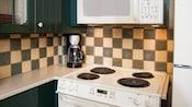 Um fogão, micro-ondas e cafeteira em uma pequena cozinha em uma Villa no Disney's Wilderness Lodge