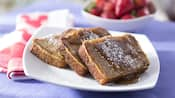 3 slices of French toast topped with syrup and powdered sugar next to a bowl of strawberries