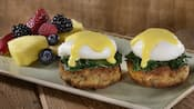 2 crab cakes topped with spinach, a poached egg and hollandaise sauce near sliced pineapple, blueberries, raspberries, blackberries, a strawberry and an apple slice