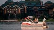 Un bateau sur l'eau avec 3hommes en train de pêcher devant le WildernessLodgeResort