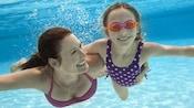 Una madre sonriente rodea con el brazo la cintura de su hija mientras nadan bajo el agua en una piscina
