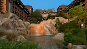A creek whose water cascades down rocks in the courtyard at Disney's Wilderness Lodge