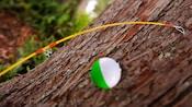 Primer plano de una caña de pescar con un flotador apoyada sobre el tronco de un árbol