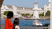 A woman and child gaze at the lake in front of Disney's Yacht Club Resort