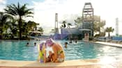 Une mère et sa fille assises au bord de la piscine Bay Cove de Bay Lake Tower à l'hôtel Disney's Contemporary Resort