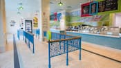 An ice cream parlor with an intricately patterned iron and wood railing to control customer flow in the waiting area, a freezer and display cases to one side, 2 long ice cream serving counters with tile and glass fronts and signage featuring their menu hanging from the ceiling