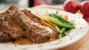 2 slices of meatloaf covered in gravy with vegetables