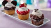 3 cupcakes on a tray, one with Mickey ears