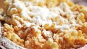 Un pastel de embudo crujiente espolvoreado con azúcar impalpable