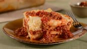 A serving of baked lasagna featuring ricotta cheese, meat, marinara and other Italian ingredients