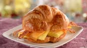 A croissant sandwich filled with bacon, cheddar cheese and scrambled egg