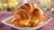 Um sanduíche de croissant recheado com bacon, queijo cheddar e ovos mexidos
