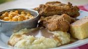 Un plato de 2presas de pollo frito con puré de papas y salsa gravy, macarrones con queso y pan de maíz