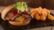 Una hamburguesa de carne cubierta con queso, cebollas, rodajas de falda de res y lechuga, al lado de una pila de croquetas de papa
