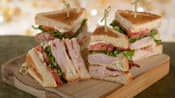 A turkey club sandwich, divided into 4 sections with each section held together by a toothpick, is served on a wooden board