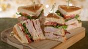 Um sanduíche club de peru dividido em 4 pedaços, com cada pedaço preso por um palito de dente, servido em uma tábua de madeira
