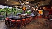 Curved sushi-bar with stools, next to floor-to-ceiling windows with a view of palm trees