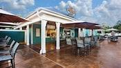 Exterior de The Paddock Grill con mesas de patio y sombrillas
