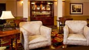 A carpeted lounge with several wooden card tables with chairs, an upholstered chair, a bronze horse table lamp, a wooden side table and a built in bar containing wine, spirits and other beverages