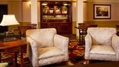Un salón alfombrado con varias mesas de juego de madera y sillas, un sillón tapizado, una lámpara de mesa con un caballo de bronce, una mesa auxiliar de madera y un bar empotrado con vino, licores y otras bebidas