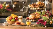 Un verre de jus d'orange et une tasse de cappuccino accompagnés de corbeilles de fruits, de pains et de pâtisseries