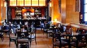 Des tables laquées d'un noir brillant pour 4personnes, avec un bar à l'autre bout de la salle
