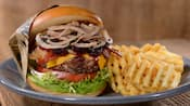 A cheeseburger topped with bacon and onions, served with waffle fries