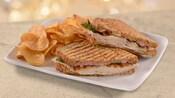 Um sanduíche de panini no prato com salgadinho chips