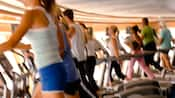 Men and women working out in blurred motion on exercise equipment