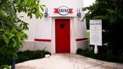 Prédio branco com porta vermelha e placa que diz