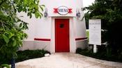 Edificio blanco con puerta roja y un letrero que dice