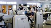 4 hombres que observan un evento deportivo por televisión en el gimnasio, rodeados de aparatos de entrenamiento Nautilus