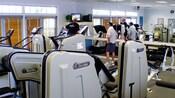 4 homens assistindo a um evento esportivo na TV no ginásio cercados por equipamentos de ginástica Nautilus