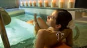 A woman lounges on the steps of a whirlpool spa with lit candles rimming the bath