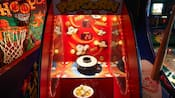 A popcorn arcade game flanked by basketball and baseball arcade games
