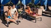 Família de 4 desfrutando de uma cabana ao lado da piscina