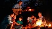 Guests enjoying a guitar player around a campfire at Disney's Fort Wilderness Resort