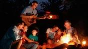 Des visiteurs profitent de la présence d'un joueur de guitare autour d'un feu au Disney'sFortWildernessResort