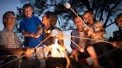 Uma família assando marshmallows ao redor da fogueira