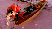 Canoe on a sandy shore adorned with tropical flowers