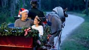 A dad and daughter enjoy an enchanting moment on a holiday sleigh ride guided a Disney Cast Member